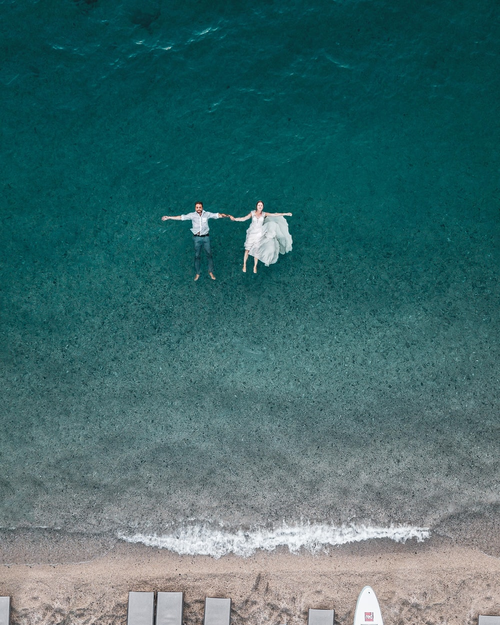 man and woman floating on blue beach