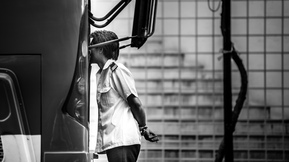 grayscale photography of man standing beside bus