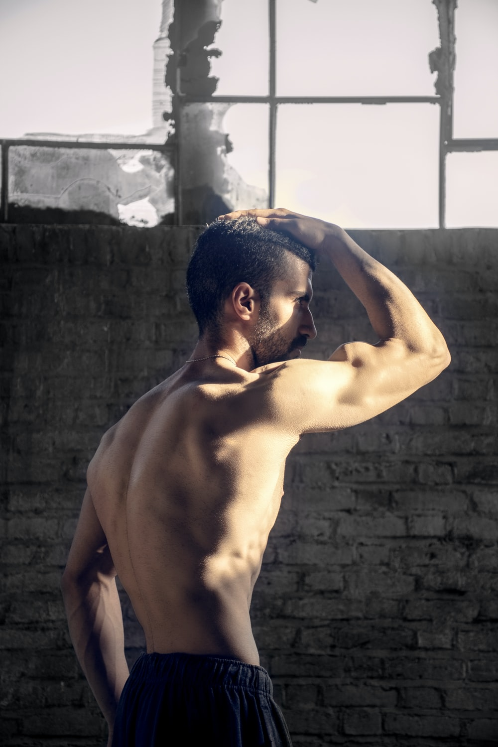 topless man placing his right hand on his head