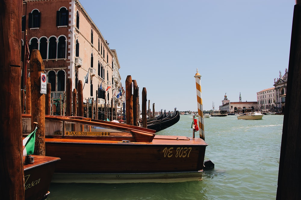brown wooden speedboat at Venice canal