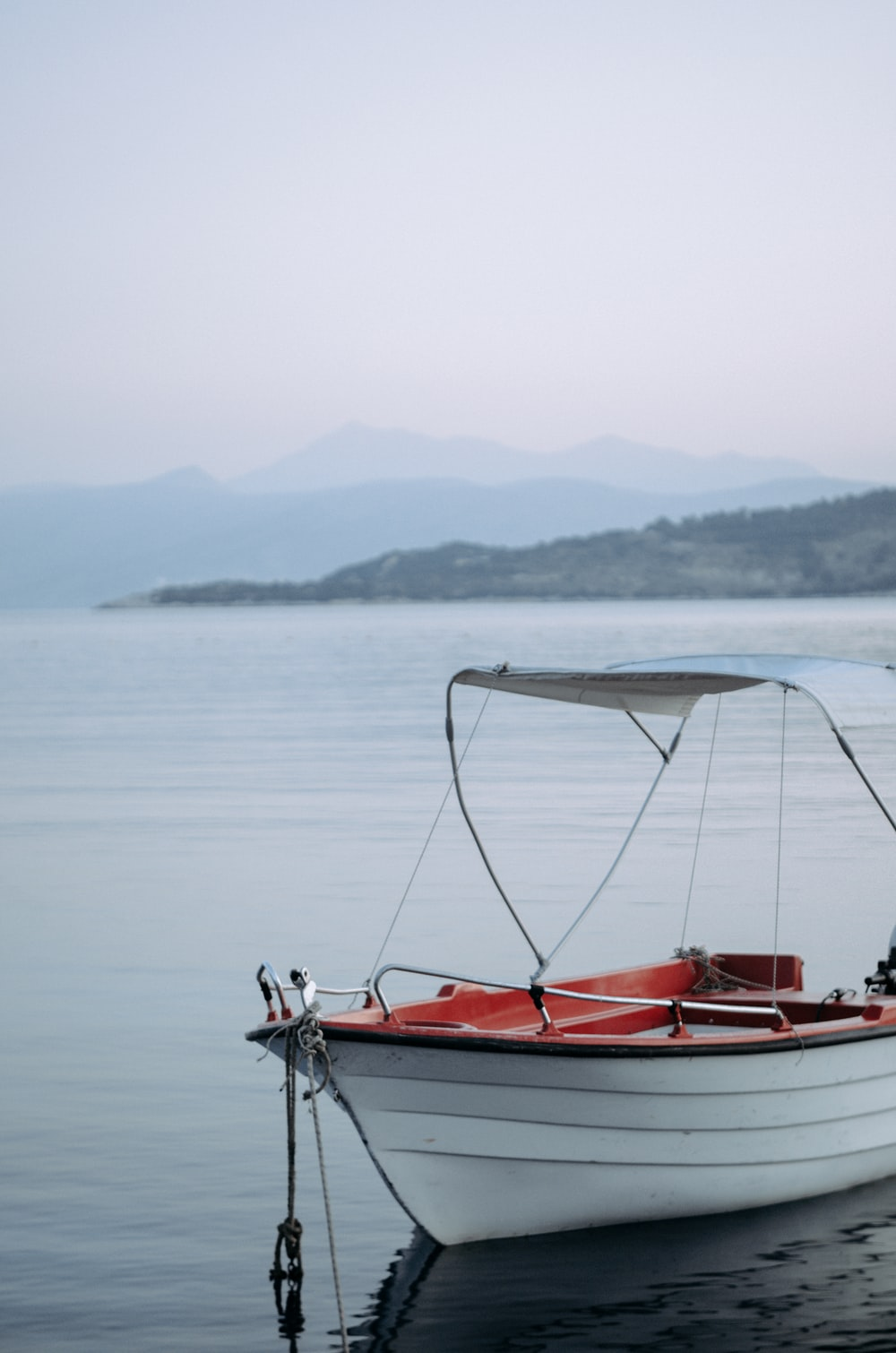 white and red boat on lake
