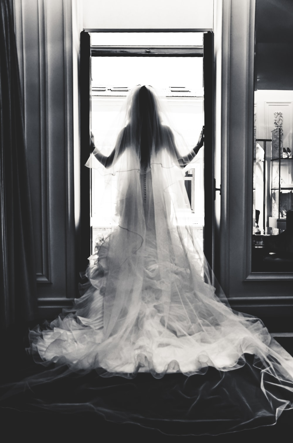 grayscale photography of woman wearing wedding gown standing near open window