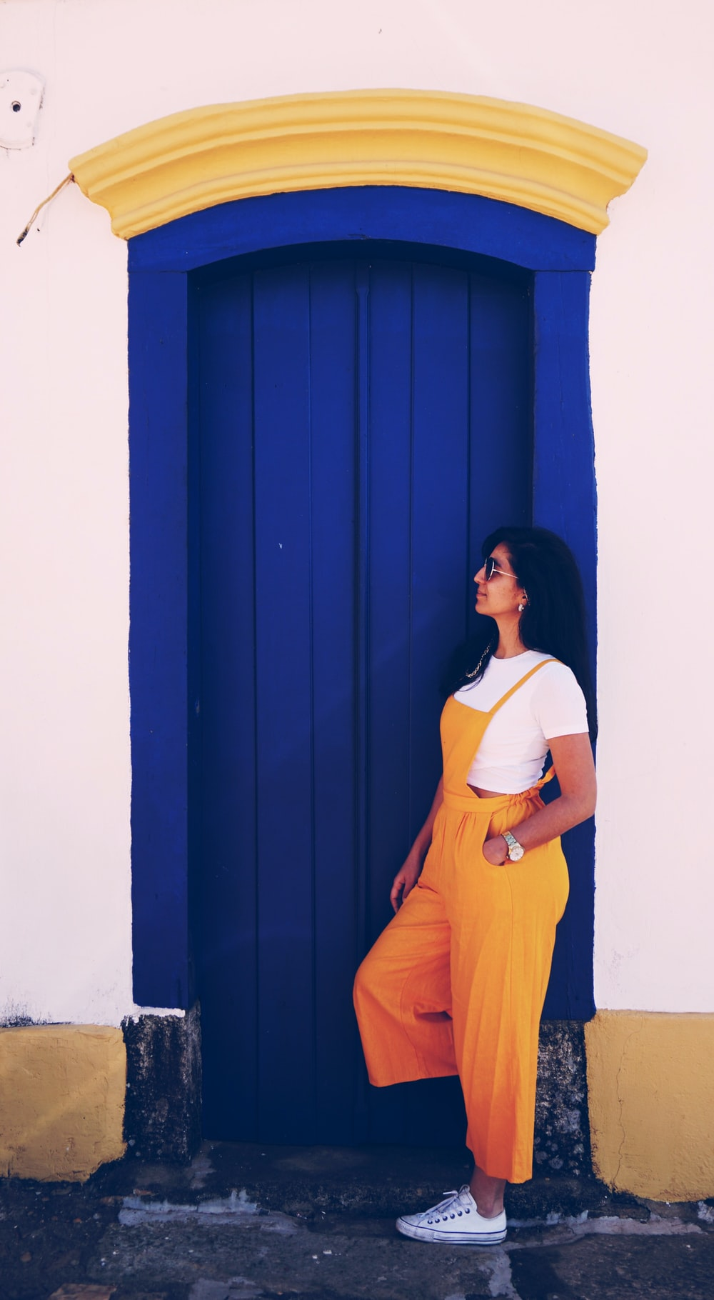 woman wearing yellow orange overalls leaning near blue painted door