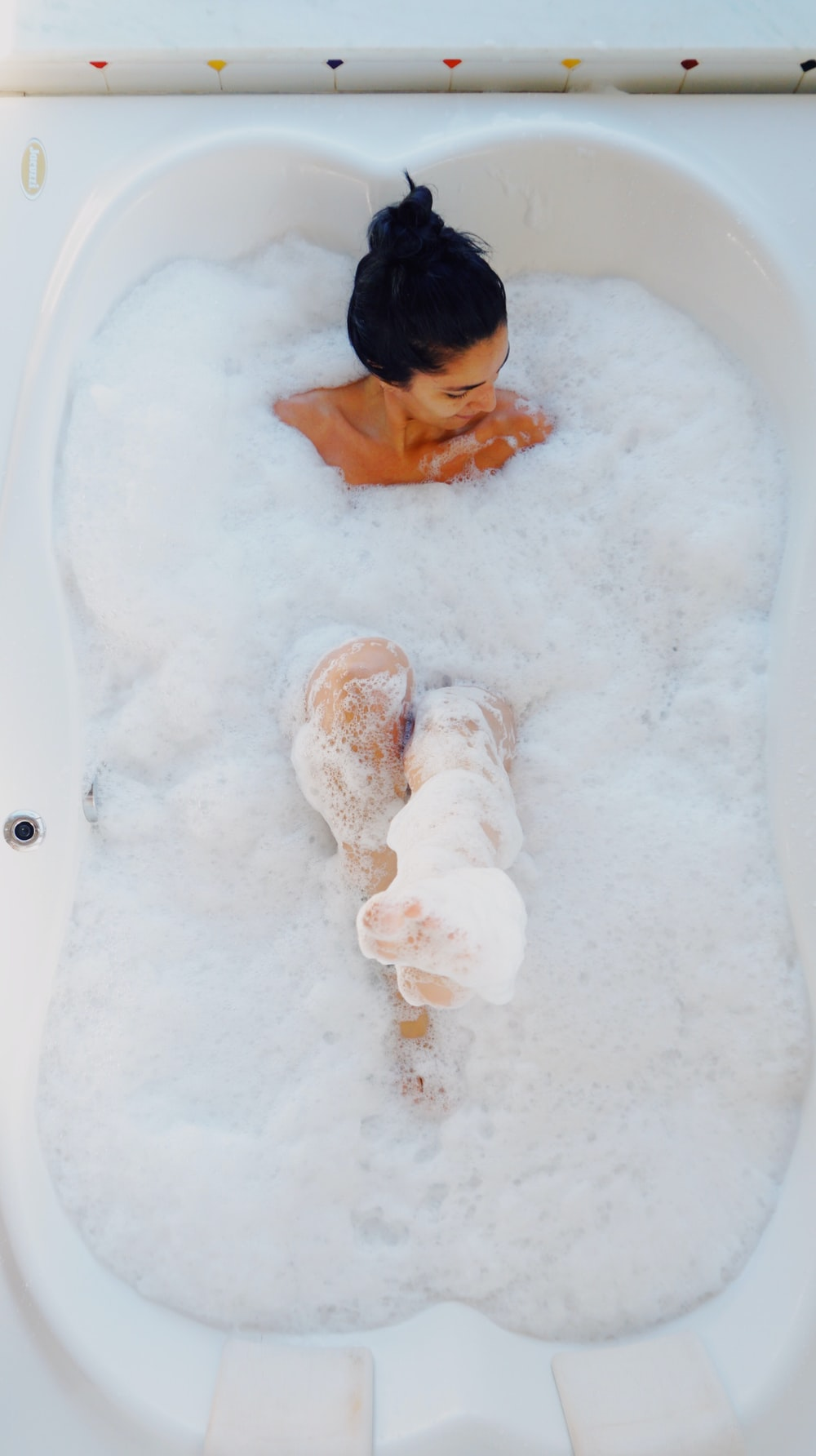 photography of woman on bathtub covered with white bubbles