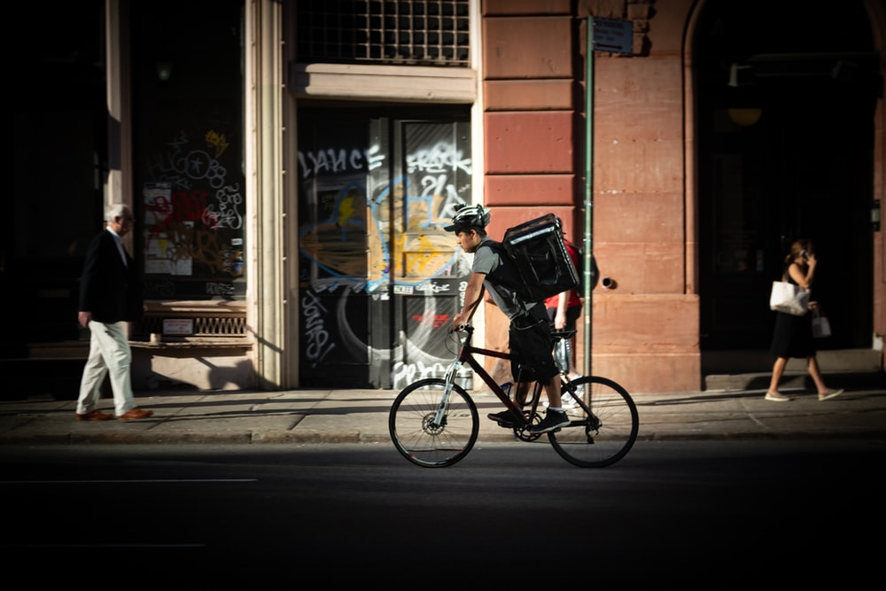 man riding bicycle near road during daytime