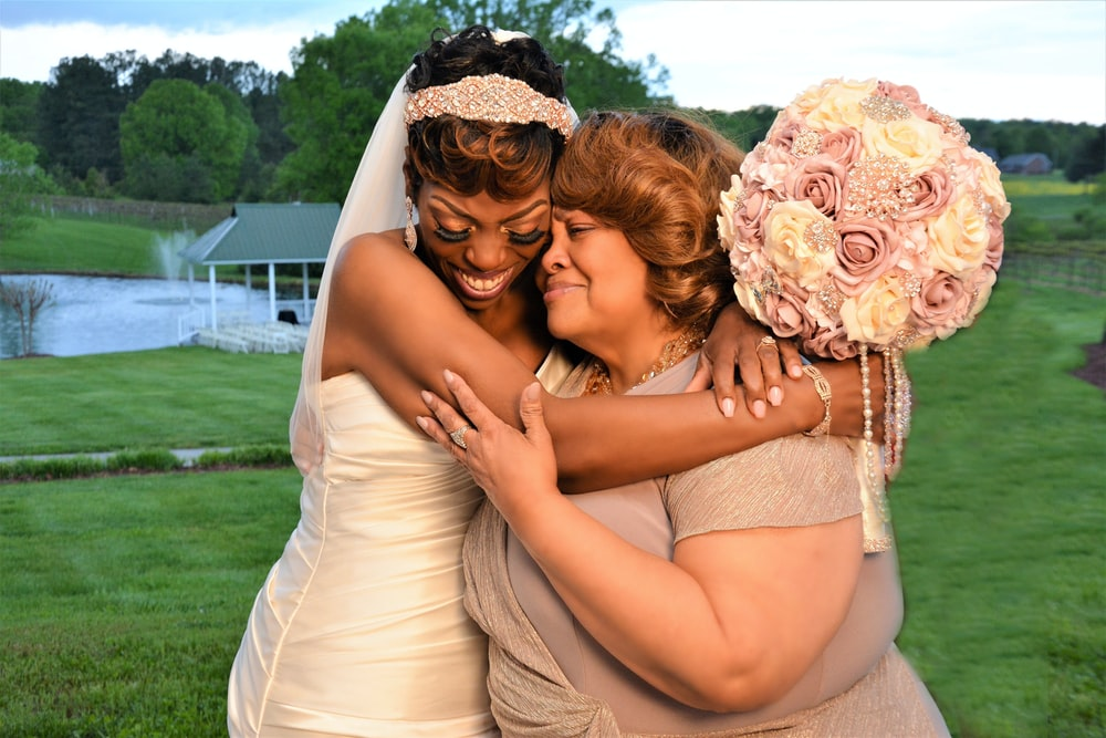 newly wedded woman hugging another woman