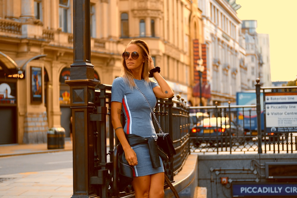 woman in blue and red short sleeved mini bodycon dress standing on top of Piccadilly Drive subway stairs