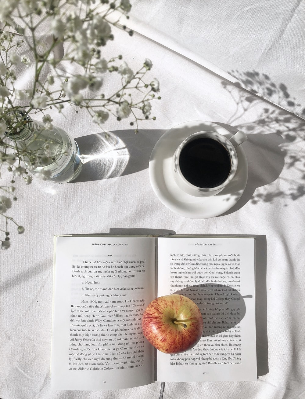 apple fruit on top of open book beside black coffee in white ceramic cup on table