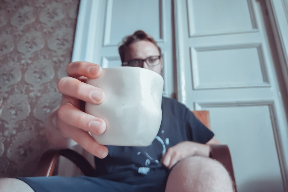man holding white ceramic cup close-up photography