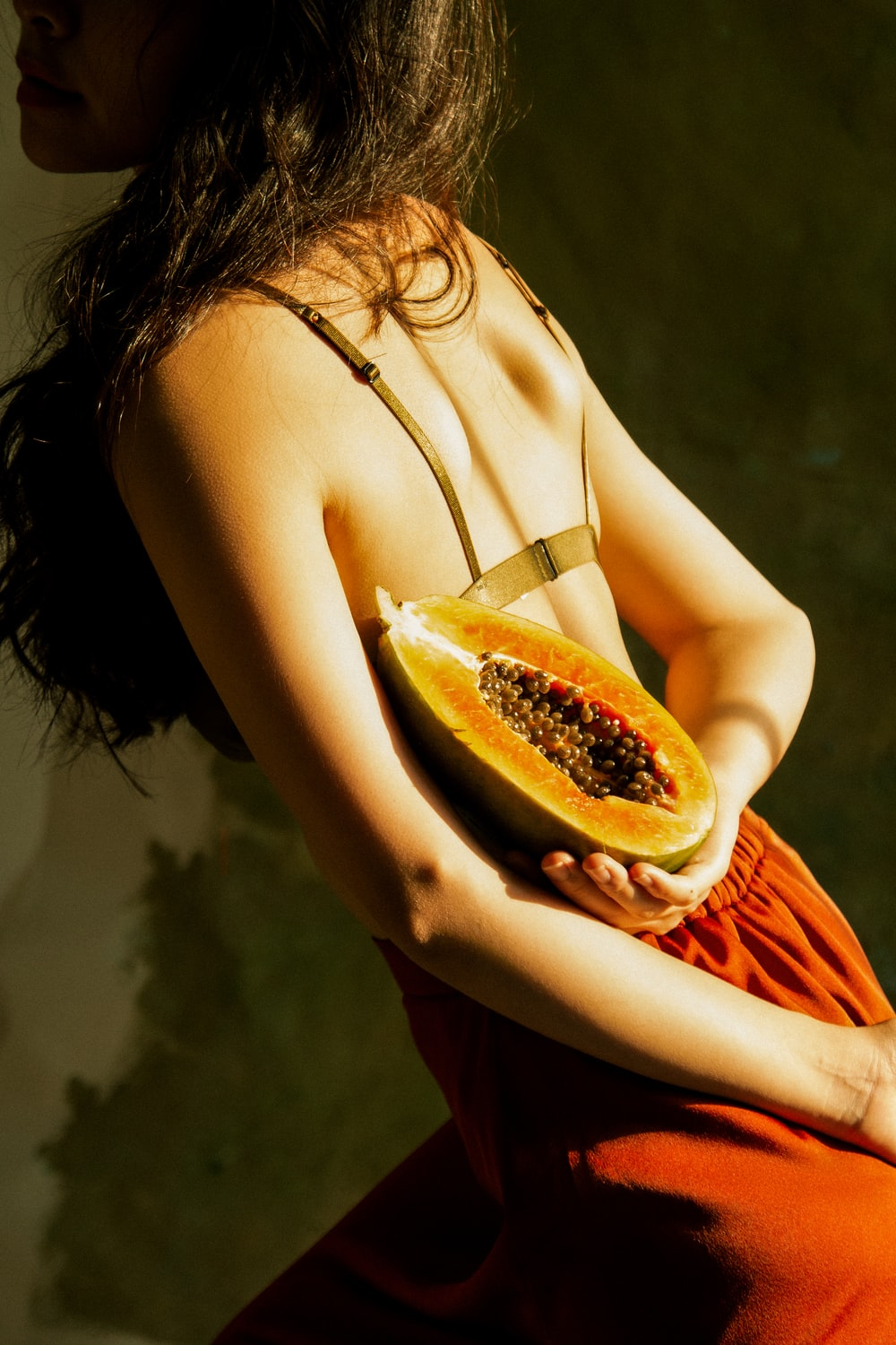 woman holding halved papaya fruit behind back