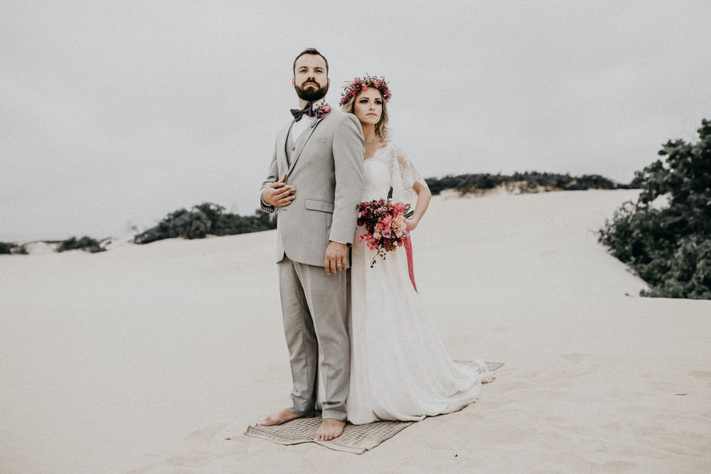 married couple standing on beach