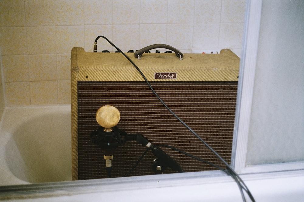 brown guitar amplifier on bath tub