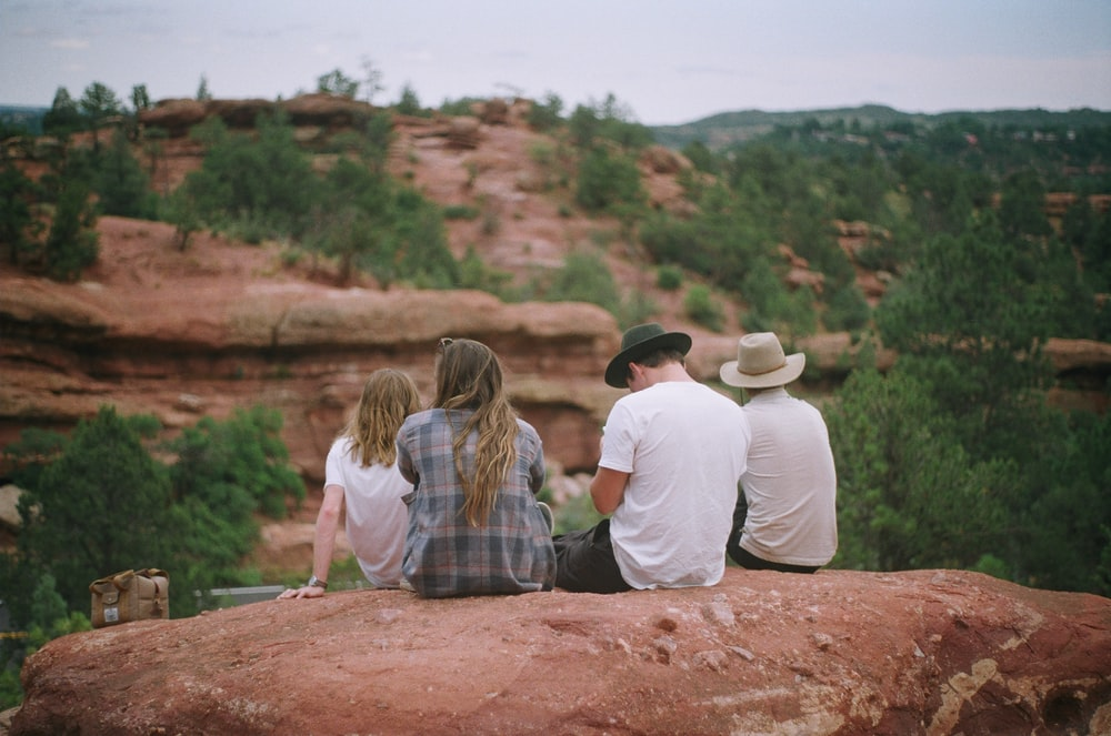 four person sitting on rock and facing hill with trees during daytime