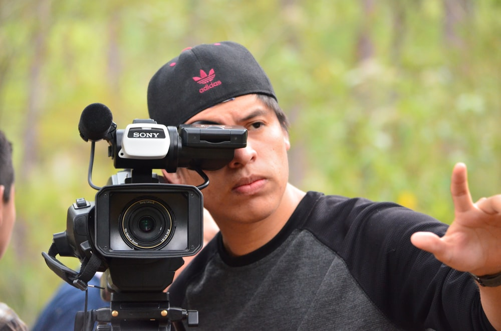 man in grey and black crew-neck shirt using video camera