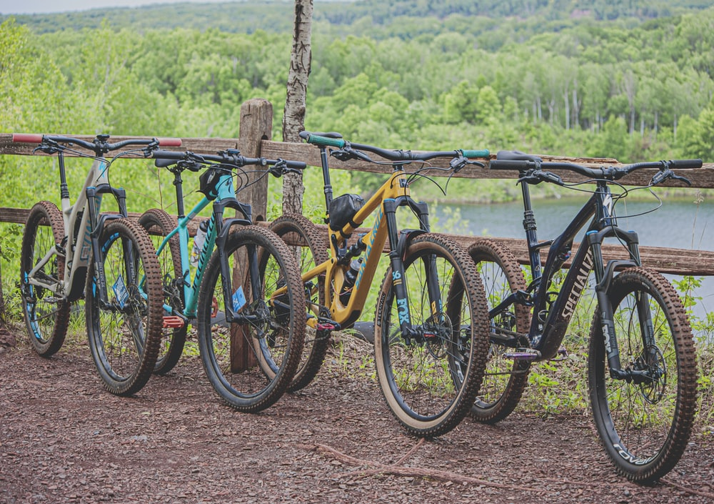 four multicolored mountain bikes parked beside brown wooden railing