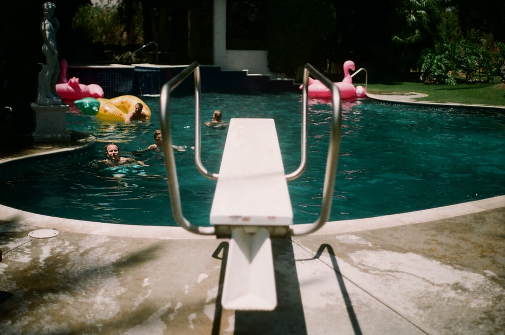 swimming pool diving board near people in pool