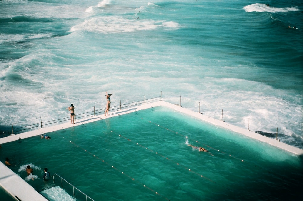 people standing and swimming on swimming pool beside the ocean