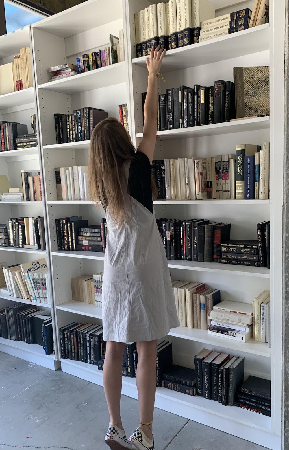 woman standing beside bookshelf