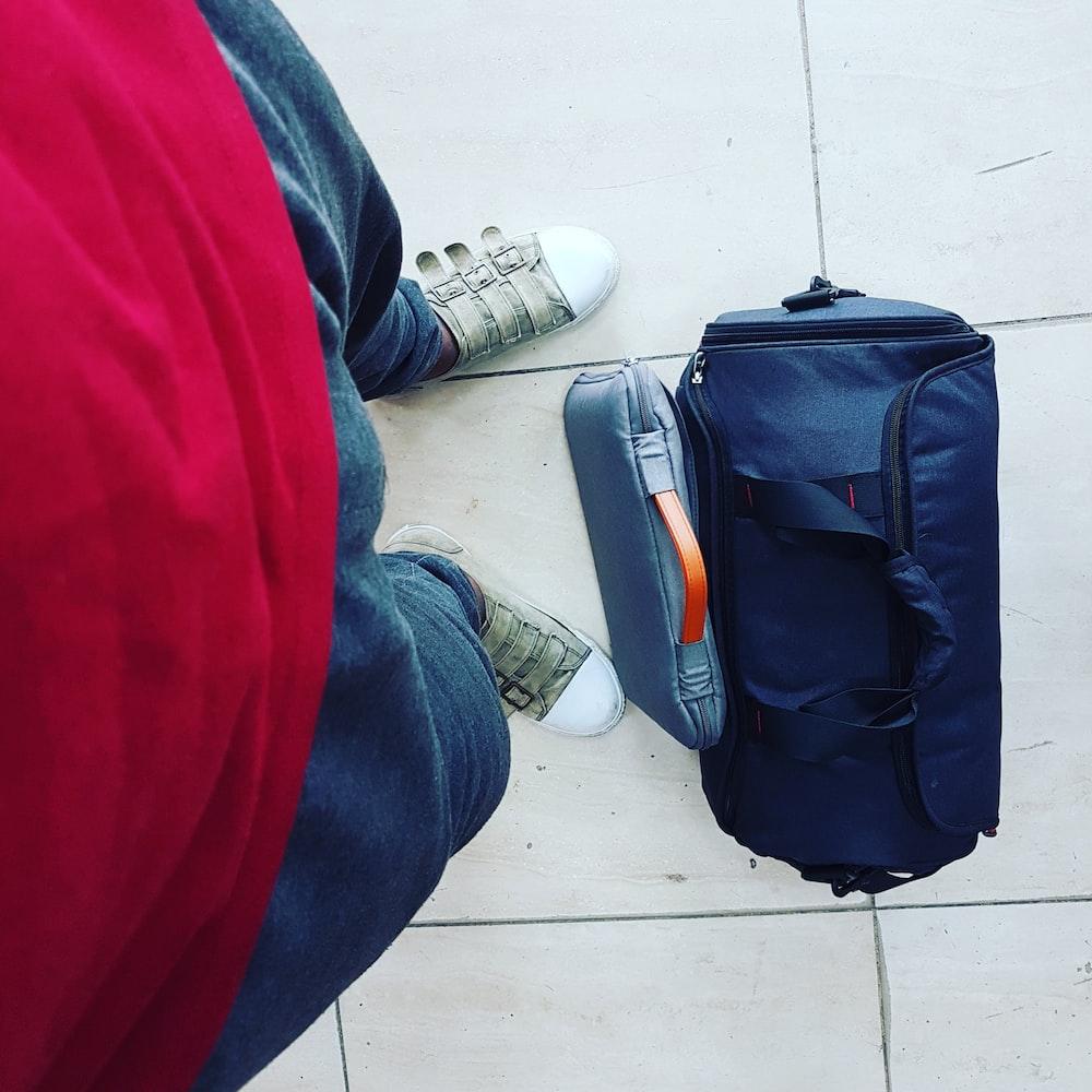 black duffel bag on white surface