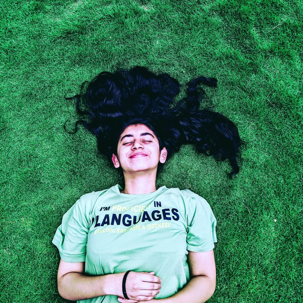 smiling woman lying on green grasses