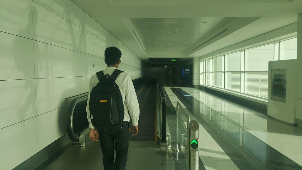man walking inside building going on escalator