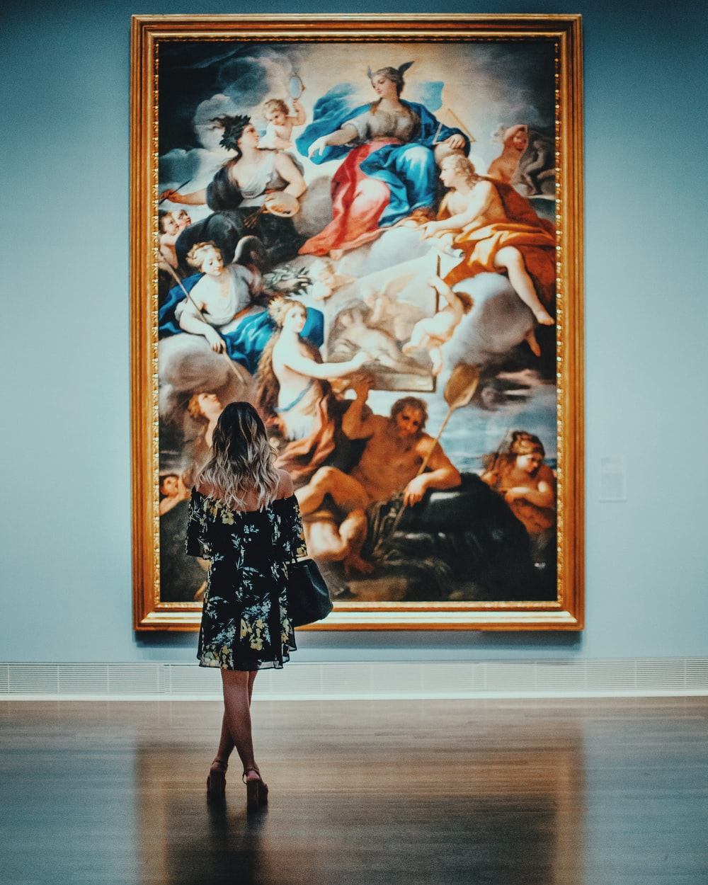 woman in black off-shoulder long sleeved mini dress standing in front of painting in museum