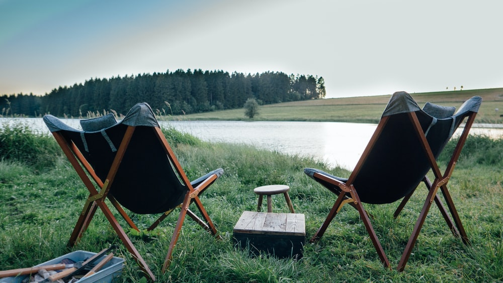 two vacant black and brown camping chairs near lake viewing green field
