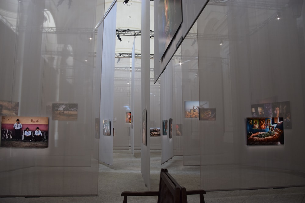multiple white curtains with image projected inside hall