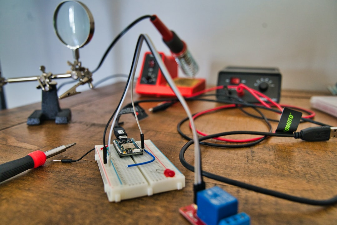 The Particle photon is an internet of things (IOT) device. In this picture it's hooked into a breadboard with an electrical relay attached to it. Also pictured in the background is a helping hand, a soldering iron, and a power supply.