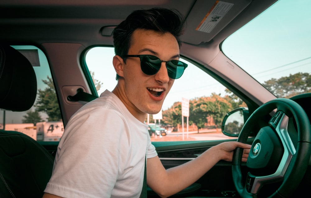 man wearing white t-shirt and sunglasses sitting on driver's seat smiling