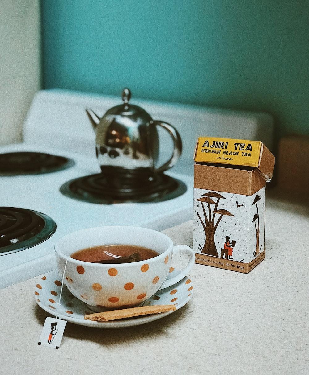 white and brown polka-dot ceramic teacup