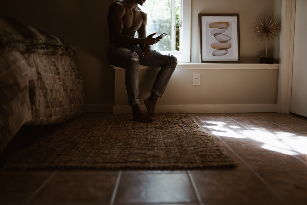 man sitting beside window while using smartphone inside room