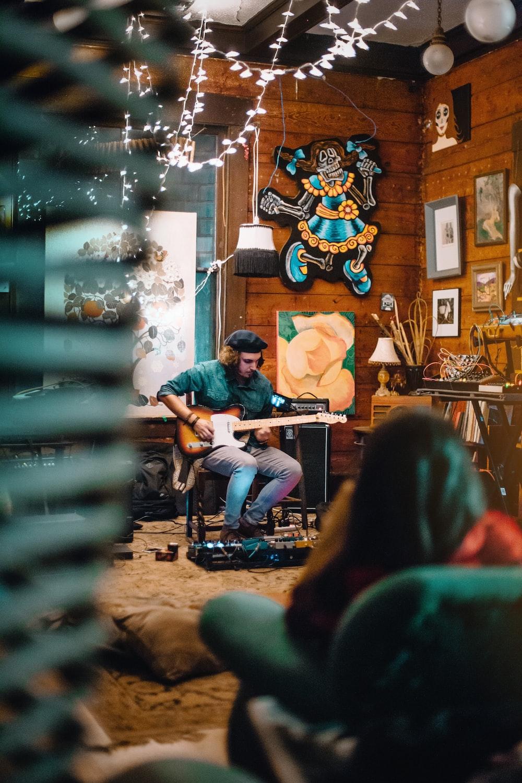 sitting man playing guitar across room