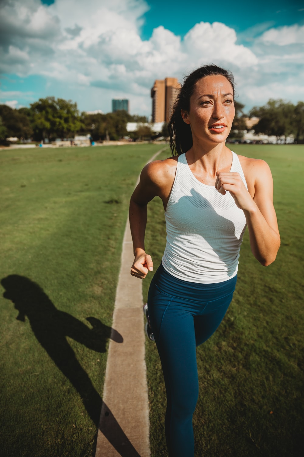woman in white tank top and blue leggings jogging in grass field