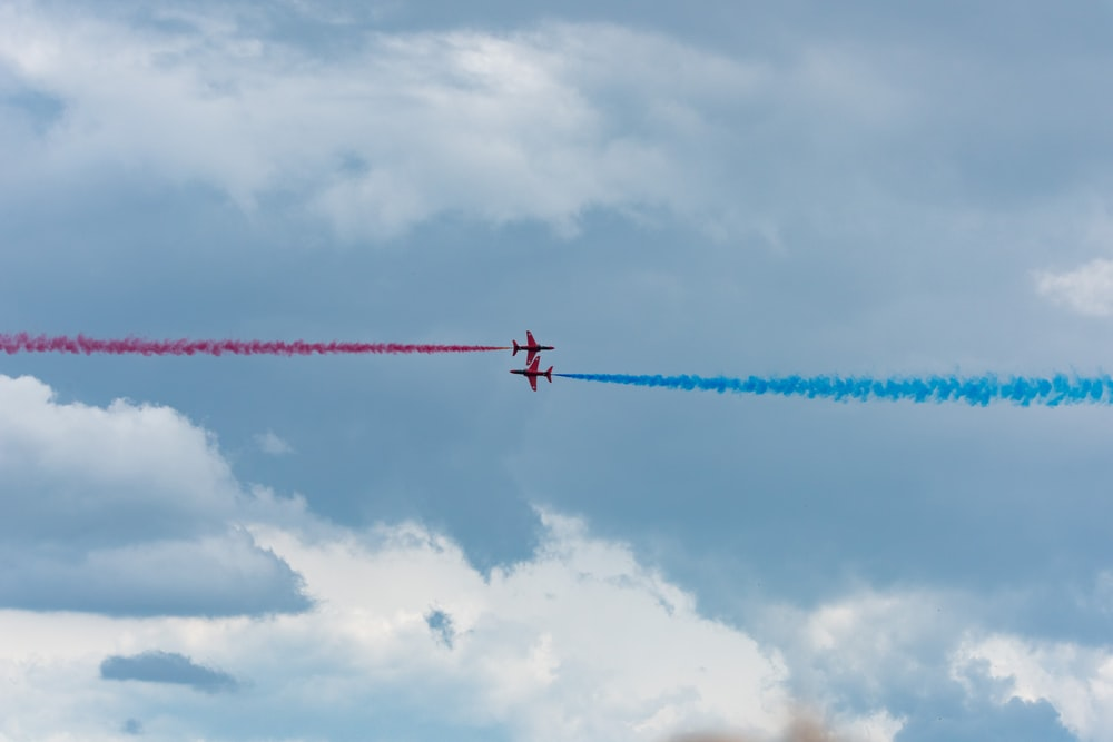 two planes with red and blue smoke
