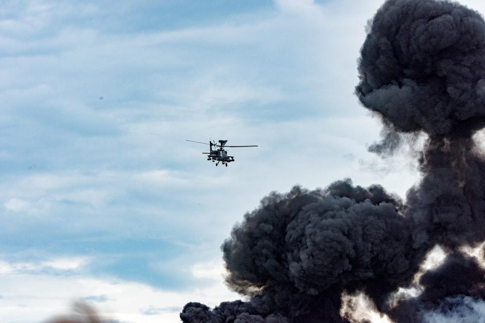 black helicopter beside black smoke