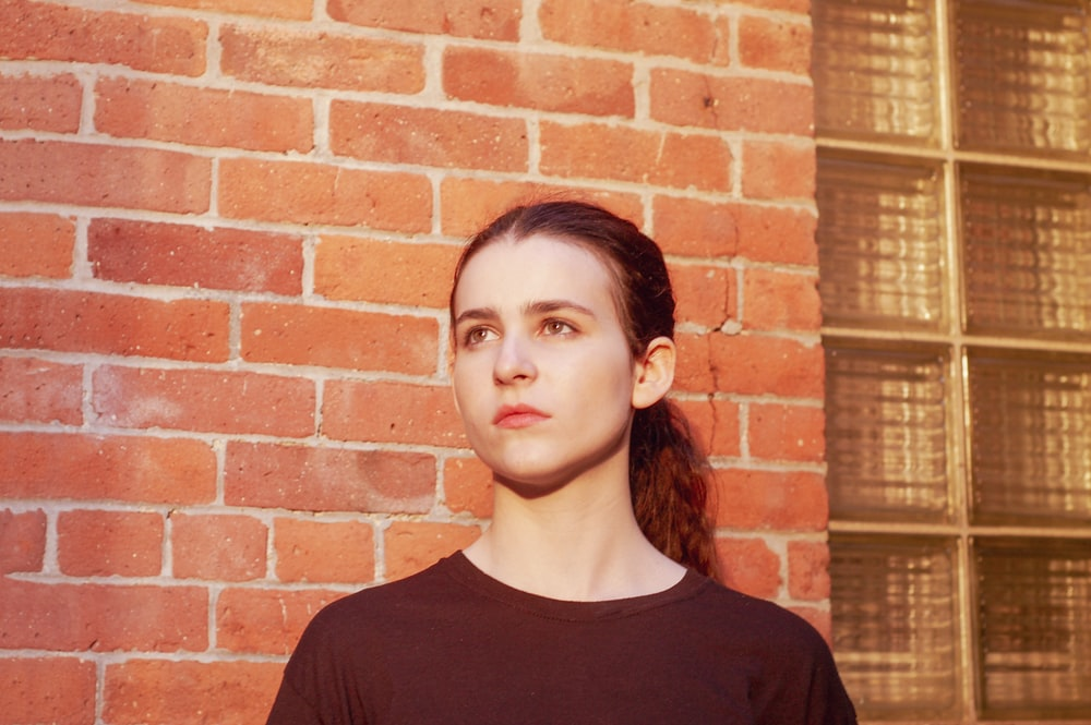 woman in red shirt in front of brick wall