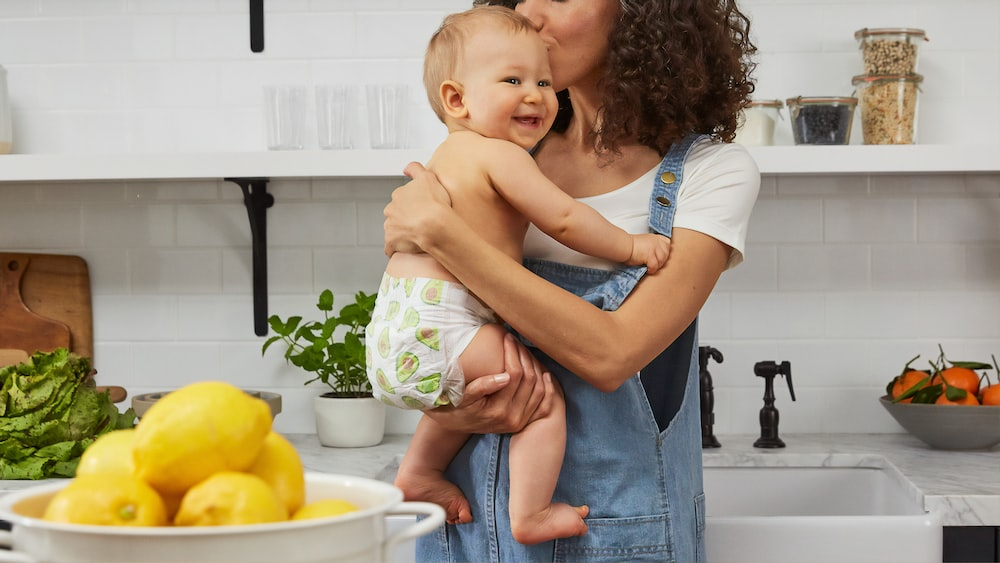 woman carrying toddler on kitchen