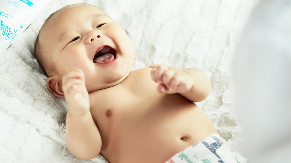 topless baby lying on bed smiling