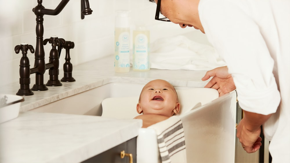 smiling baby in sink beside smiling person