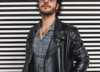 man wearing standing beside wall
