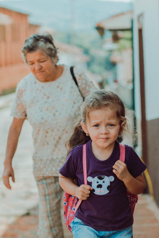 girl walking in front of walking woman