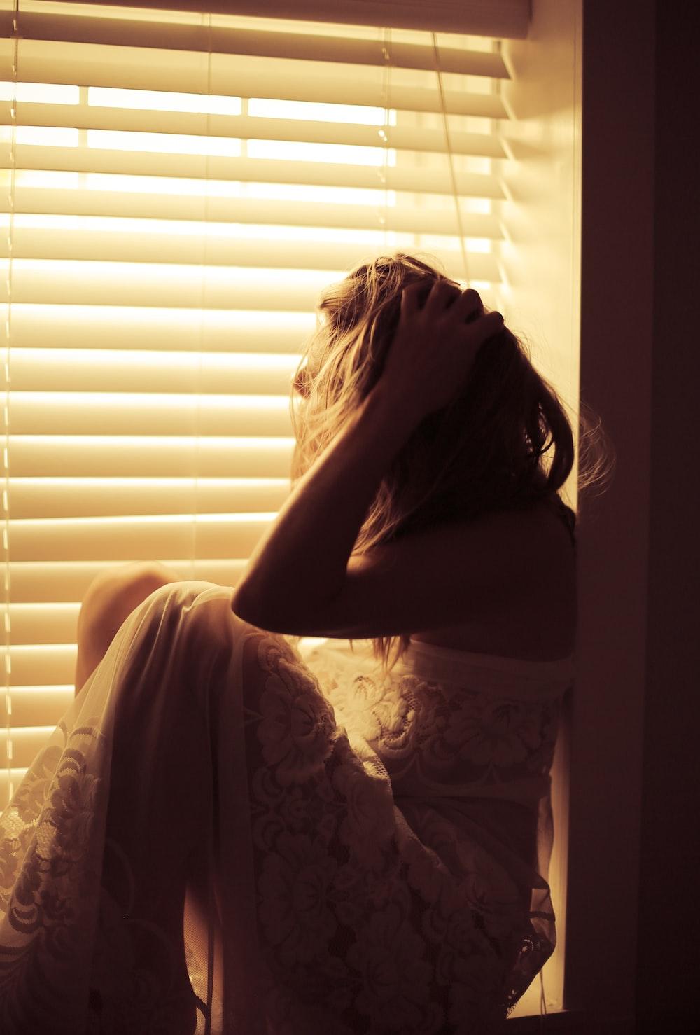 woman in white lace dress sitting beside window blinds