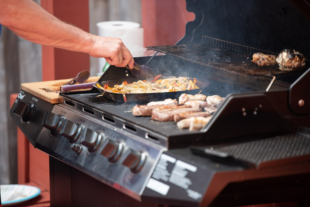 person grilling meats in gas grill