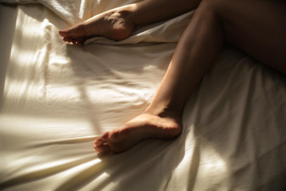 human legs on white textile