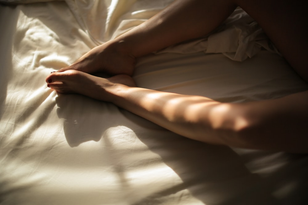human feet on white bedspread close-up photography