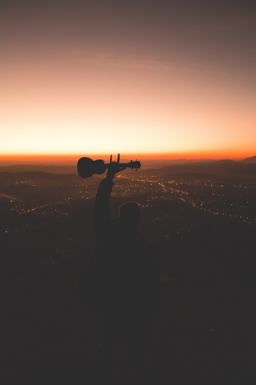 silhouette photography of person holding guitar