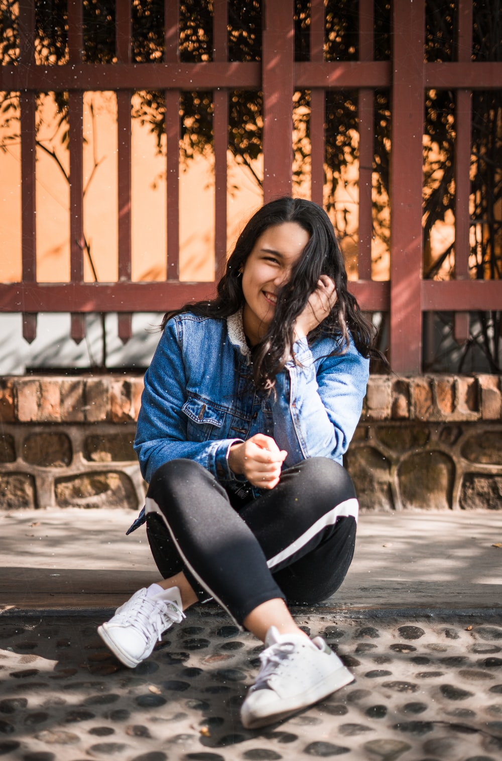 smiling woman wearing blue denim jacket and black leggings