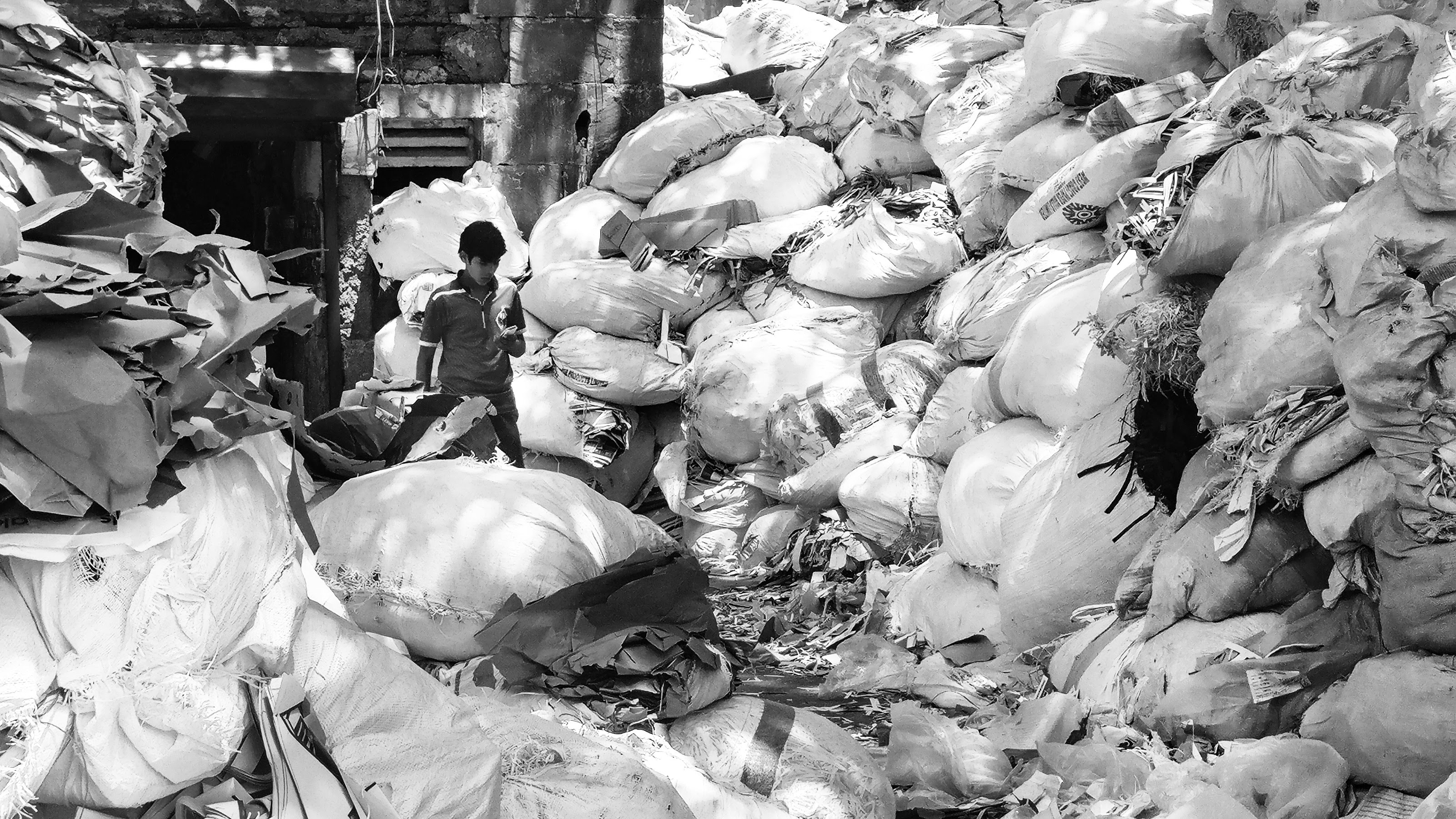 grayscale photo of man standing beside file of sack