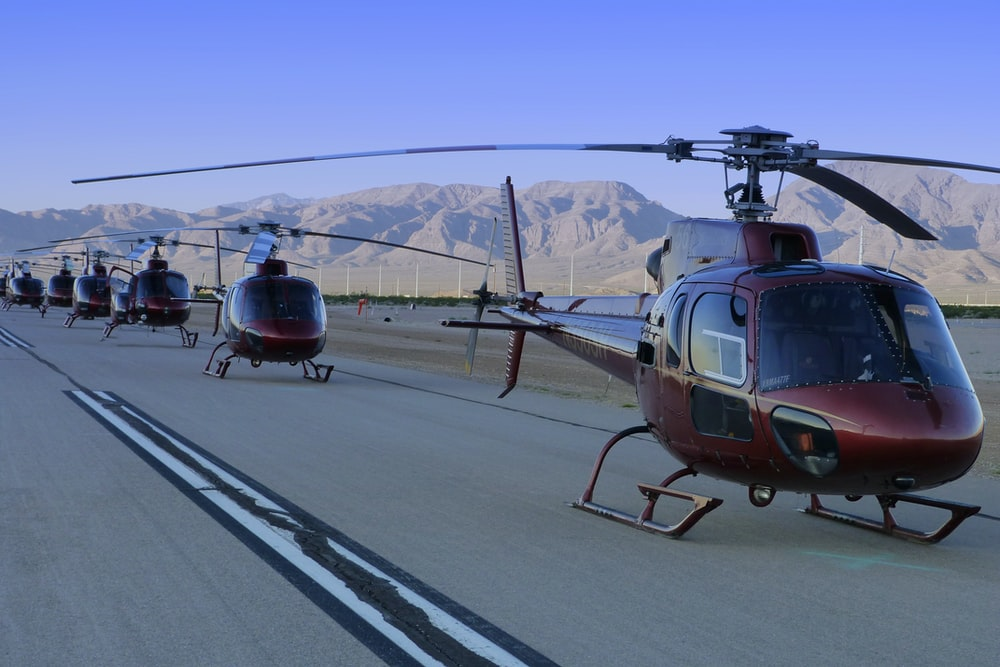 photography of red helicopters on road during daytime
